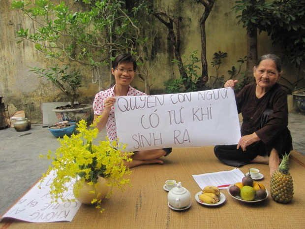 "Hai Phong, 9 am, 5 May 2013: former political prisoner Pham Thanh Nghien and her mother in their back yard. The sign reads: ""[We have] human rights since we were born."""